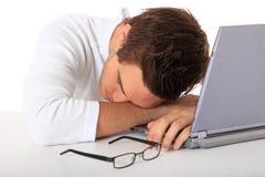 Estudiante que toma una siesta en su computadora portátil Fotografía de archivo libre de regalías