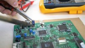 Estudiante que trabaja con los componentes electrónicos usando el soldador almacen de video