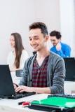 Estudiante que trabaja en la PC del ordenador portátil en universidad Foto de archivo libre de regalías