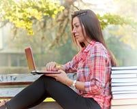 Estudiante que usa el ordenador portátil en banco de parque Imagen de archivo libre de regalías