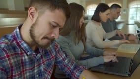 Estudiante que usa el ordenador portátil en la sala de conferencias almacen de video
