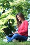 Estudiante que usa la computadora portátil en parque Fotos de archivo libres de regalías