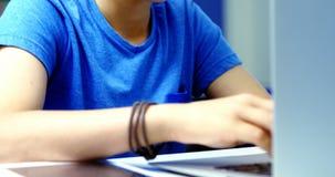 Estudiante que usa la computadora portátil en sala de clase almacen de metraje de vídeo