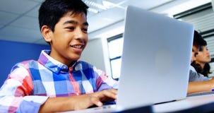 Estudiante que usa la computadora portátil en sala de clase almacen de video