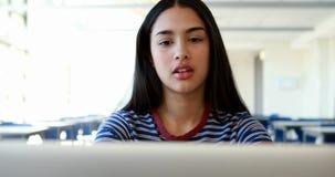 Estudiante que usa la computadora portátil en sala de clase metrajes