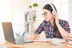 Estudiante que usa la tableta digital que escucha Imagen de archivo libre de regalías