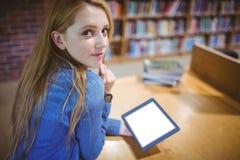 Estudiante que usa la tableta en la biblioteca que mira detrás la cámara Foto de archivo