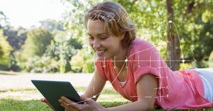 Estudiante que usa la tableta mientras que miente en hierba imagen de archivo
