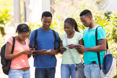 Estudiante que usa los teléfonos celulares Imagenes de archivo