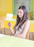 Estudiante que usa smartphone en sala de clase Imagen de archivo libre de regalías