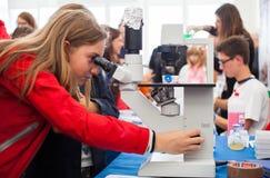 Estudiante que usa un microscopio Imágenes de archivo libres de regalías