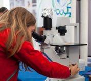 Estudiante que usa un microscopio Fotografía de archivo libre de regalías