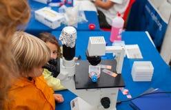 Estudiante que usa un microscopio Imagen de archivo libre de regalías