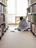 Estudiante Reaching For Book en biblioteca Foto de archivo