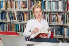Estudiante Reading del libro en una biblioteca Fotos de archivo libres de regalías
