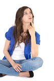 Estudiante reflexivo joven aislado que se sienta en piernas cruzadas. Foto de archivo