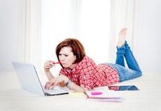 Estudiante rojo del pelo, mujer de negocios que miente abajo trabajando en el ordenador portátil Foto de archivo libre de regalías