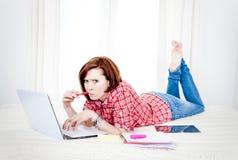Estudiante rojo del pelo, mujer de negocios que miente abajo trabajando en el ordenador portátil Foto de archivo