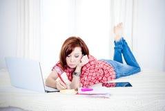 Estudiante rojo del pelo, mujer de negocios que miente abajo trabajando en el ordenador portátil Imágenes de archivo libres de regalías