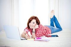 Estudiante rojo feliz del pelo, mujer de negocios que miente abajo trabajando en el ordenador portátil Fotos de archivo libres de regalías