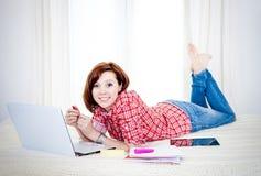 Estudiante rojo feliz del pelo, mujer de negocios que miente abajo trabajando en el ordenador portátil Fotos de archivo