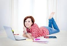 Estudiante rojo feliz del pelo, mujer de negocios que miente abajo trabajando en el ordenador portátil Imagen de archivo libre de regalías