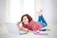 Estudiante rojo feliz del pelo, mujer de negocios que miente abajo trabajando en el ordenador portátil Imágenes de archivo libres de regalías