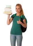 Estudiante rubio con la pila de libros y de mochila, feliz de conseguir el kn Fotografía de archivo