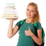 Estudiante rubio con la pila de libros y de mochila, feliz de conseguir el kn Foto de archivo