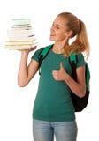Estudiante rubio con la pila de libros y de mochila, feliz de conseguir el kn Fotos de archivo
