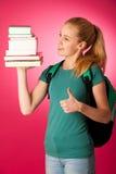 Estudiante rubio con la pila de libros y de mochila, feliz de conseguir el kn Imágenes de archivo libres de regalías