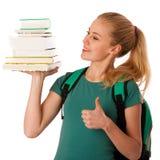 Estudiante rubio con la pila de libros y de mochila, feliz de conseguir el kn Fotos de archivo libres de regalías