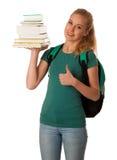 Estudiante rubio con la pila de libros y de mochila, feliz de conseguir el kn Foto de archivo libre de regalías