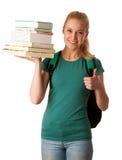 Estudiante rubio con la pila de libros y de mochila, feliz de conseguir el kn Imagen de archivo