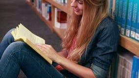 Estudiante rubio feliz que lee un libro almacen de metraje de vídeo