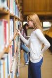 Estudiante rubio que busca el libro en estantes de la biblioteca Foto de archivo