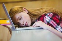 Estudiante rubio que duerme en el ordenador portátil Fotografía de archivo