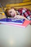 Estudiante rubio que duerme en el ordenador portátil Imágenes de archivo libres de regalías