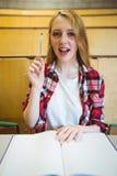Estudiante rubio que hace una pregunta durante clase Foto de archivo libre de regalías