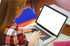 Estudiante rubio que usa el ordenador portátil durante clase Foto de archivo libre de regalías
