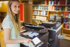 Estudiante rubio sonriente que hace una copia Foto de archivo libre de regalías