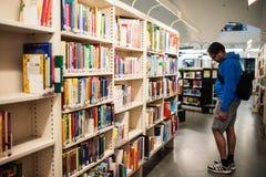 Estudiante searcing para los libros en la ciudad de la biblioteca principal Metso de Tampere Imagen de archivo libre de regalías