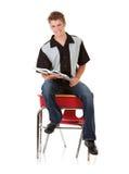 Estudiante: Sentada masculina adolescente en el escritorio de la escuela Foto de archivo libre de regalías