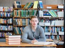 Estudiante serio en una biblioteca que mira la cámara Fotografía de archivo libre de regalías