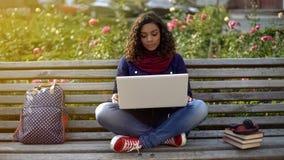 Estudiante serio que habla con los amigos sobre la cámara del ordenador portátil, sentándose en banco Fotografía de archivo libre de regalías