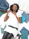Estudiante serio que hace su preparación que miente en una cama Imágenes de archivo libres de regalías