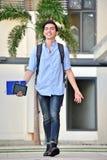 Estudiante sonriente With Books Walking del muchacho de la minoría en campus imagen de archivo libre de regalías