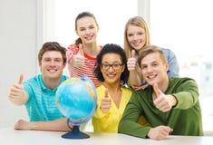Estudiante sonriente cinco con el globo de la tierra en la escuela Fotografía de archivo libre de regalías