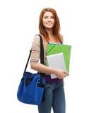 Estudiante sonriente con el bolso, las carpetas y PC de la tableta Foto de archivo libre de regalías