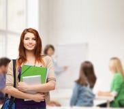 Estudiante sonriente con el bolso, las carpetas y PC de la tableta Fotografía de archivo